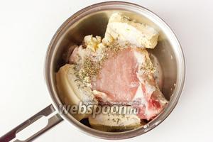 Свиную корейку кладём в небольшую кастрюлю или ковш. Мясо должно занимать почти весь объём кастрюли. Также выкладываем к мясу сливочное масло, сразу же добавляем специи (соль, молотые перцы и смесь сухих трав).