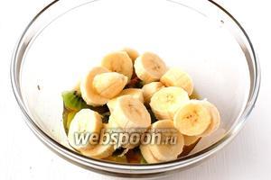 Бананы порезать кружочками, выложить в посуду с соусом.