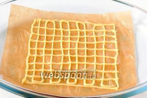 На смазанной маслом кондитерской бумаге с помощью шприца нарисовать сеточку из теста размером 10х11 см.