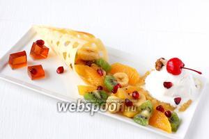 Выложить  фруктовый салат на блюдо так, чтобы он визуально высыпался из сахарного рожка. Поместить шарик мороженого на подушку из манго. Сервировать коктейльной вишней, кусочком ореха, кубиками желе из глинтвейна