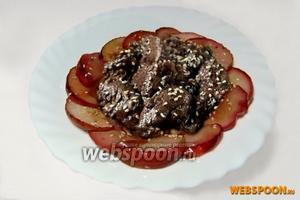 Выкладываем яблоки венком на тарелку, в центр кладём горкой печень, поливаем соусом, в котором она тушилась, и посыпаем поджаренными кунжутными семечками. Очень вкусно!