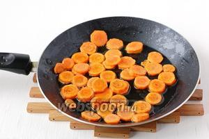 Морковь почистить, порезать кружочками, обжарить по 1 минуте с каждой стороны.