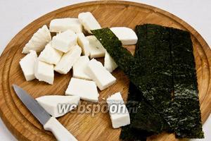 Нарезать сыр прямоугольниками (примерно 2х4 см), а нори разрезать так, чтобы получились длинные полоски.
