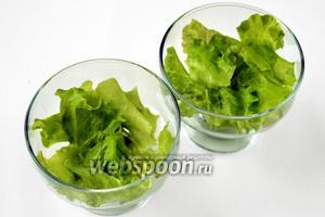 Вымытый и обсушенный салат рвём кусочками на дно креманок, расправляем красивые части листа к краям креманок.