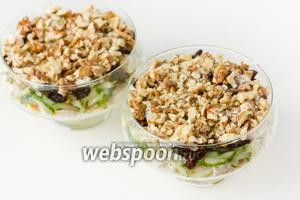 Чернослив поливаем также майонезом и выкладываем поверх него грецкие орехи, распределяя их по поверхности салата.
