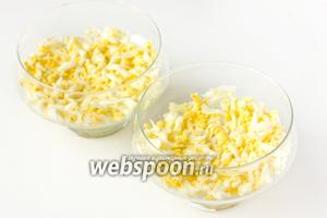 Собираем салат. На дно стеклянных креманок выкладываем первым слоем измельчённые куриные яйца.
