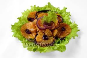 Выкладываем на блюдо вымытые и обсушенные листья салата, кладём кружки апельсина, извлеченные из соуса, украшаем разобранным на кольца луком, при необходимости поливаем сверху небольшим количеством соуса.