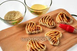 Остывшее печенье с помощью кисточки смазываем по бокам сгущённым молоком и окунаем в кунжутное семя, дав ему прилипнуть.