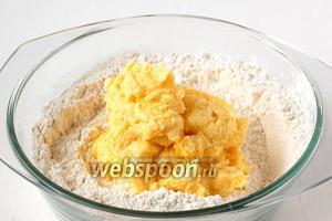 В центр мучной смеси выложить масляную и несколькими движениями руки или ложки соединить всё в однородную массу. Долго месить песочное тесто нельзя.