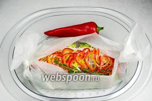 Выложить рыбу с овощами в судок пароварки. Добавить один сладкий перец. Когда он запарится, использовать его для украшения блюда. Варить на пару в течение 20 минут.