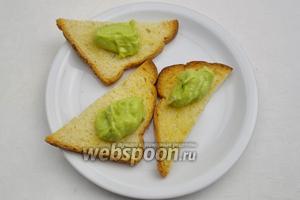 На каждую гренку выложить помазку из авокадо. Украсить зеленью. Гренки подавать для перекуса.