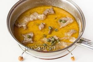 Перекладываем всё содержимое сковороды (мясо вместе с соусом) в сотейник или небольшую кастрюлю, доливаем кипячёную воду, накрываем крышкой, доводим на сильном огне до кипения, уменьшаем огонь до минимального и тушим свинину в кефире около 40 минут. Через 40 минут добавляем в сотейник каперсы и измельчённый чеснок. Перемешиваем, 3 минуты прогреваем и снимаем сотейник с плиты.