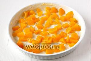 Персики нарезать небольшими кусочками и выложить в смазанную маслом форму для запекания.