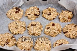 Разогреть духовку до 200ºC, застелить противень пергаментной бумагой и порционно ложкой выкладывать овсяно-фруктовую массу на противень, формируя круглые печенья.