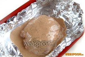 Кладём в форму для запекания или на противень 3-4 слоя фольги, края приподнимаем. Перекладываем мясо и выливаем туда же остатки заливки.