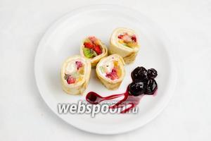 Выложить куски блина разного размера красиво на тарелку в виде роллов. Полить вишневым сиропом. Подавать на десерт.