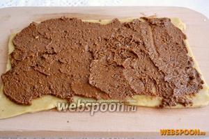 Тесто разделите на удобные небольшие части. Раскатайте его в прямоугольник толщиной 0,3 см и смажьте ореховым пралине.