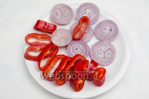 Нарезать овощи для шашлыка — лук и перец кольцами.