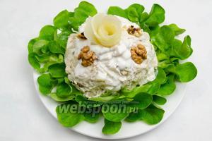 Аккуратно переносим салатный шар на листья салата в тарелку. Сверху полить оставшимся соусом. Украсить дольками грецких орехов. Верх салата украсить нежным цветком из груши. Тонкие полоски с груши нарезать с помощью овощерезки. Сбрызнуть их соком лимона. Сформировать лепестки груши в цветок.