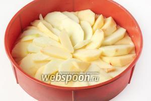 Выкладываем тесто в высокую форму для выпечки (обязательно высокую, так как пирог хорошо поднимется!). Яблоки чистим, удаляем сердцевину и нарезаем ломтиками. Выкладываем на тесто ломики яблок. Ставим пирог в предварительно разогретую до 180 ºC духовку и выпекаем 20 минут.