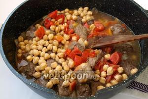 Добавить к мясу помидоры, замоченный нут, аджику и красный молотый перец. Залить водой, дать закипеть. Накрыть крышкой и тушить 1 час.