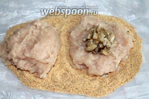 Ложкой фарш выложить на панировочные сухари, разровнять, сформировав лепёшку. В центр положить чайную ложку грибной начинки, в которую можно добавить яичный желток, чтобы грибы связались.