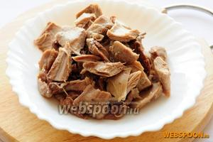Снимите шкурку, отделите мясо от костей и нарежьте на куски.