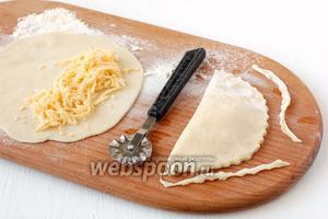 Выложить на половину лепёшки 2 столовых ложки сыра. Соединить концы лепешки, фигурно обрезать края.