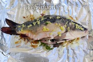 На луковую подушку кладём рыбу, натираем ёе снаружи и изнутри приготовленным имбирно-лимонным маринадом, а также фаршируем оставшимся луком и зеленью. Плотно завернув рыбу в фольгу, отправляем её в духовку на 1 час при температуре 190 °С.