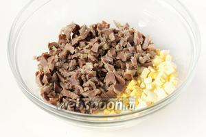 Соединяем в глубоком салатнике яйца и нарезанные мелкими кубиками куриные желудочки.