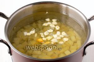 В кастрюлю с кипящей водой бросить подготовленный картофель и порезанный пластинками чеснок. Посолить по вкусу.