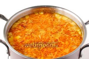Добавить жареную морковь в кипящий суп.