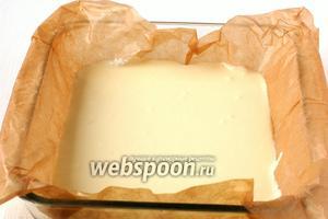 Форму размером 14х14 см выложить кулинарной бумагой и вылить на дно творожную массу.