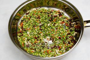 Смесь гороха с овощами высыпать на сухую сковороду, прожарить в течение 5 минут, всё время помешивая.