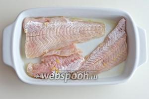 Смажьте оливковым маслом форму для запекания и разместите в ней рыбу.