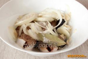 Сложить рыбу в миску, добавить лук, почищенный и измельчённый чеснок. Посолить, поперчить, добавить сахар, соль, приправу для рыбы, чёрный молотый перец, растительное масло и уксус.