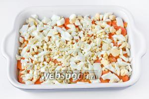 Отваренные яйца чистим и нарезаем средними кусочками. Выкладываем яичный слой поверх морковного.