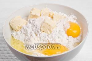 Добавляем в мучную смесь размягчённое масло, 1 яйцо и отделённый желток и тщательно перемешиваем.
