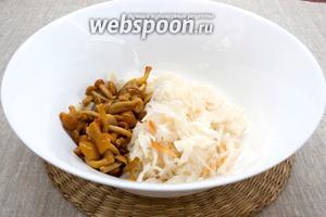 В миску поместить квашенную капусту и маринованные опята.