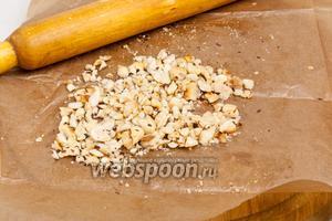 Подсушить на сухой сковороде орехи, снять шелуху и измельчить в ступке или скалкой.
