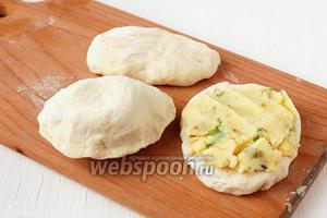 На каждый кусочек теста выложить по 2 полных столовых ложки картофельной массы. Сложить лепёшку и защипнуть края.