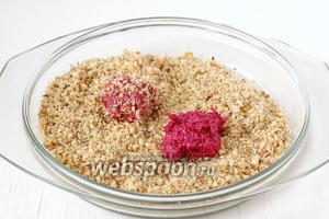 Набирать свекольную массу чайной ложкой и обваливать её в  измельчённых орехах, формируя шарики.
