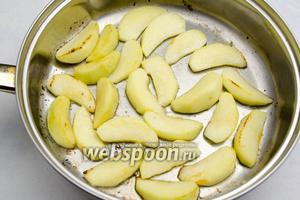 Выложить дольки яблок на сковороду. Обжаривать яблоки до румяного вида, чтобы они немного смягчились.
