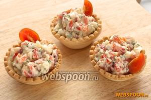 Наполнить тарталетки и украсить их кусочками помидора черри или веточкой зелени.