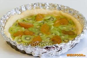 Сверху на киви выложите кусочки персиков из варенья. Все кусочки киви смажьте вареньем.