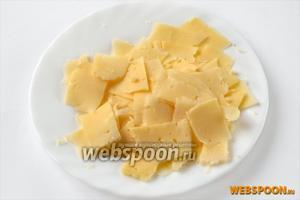 С помощью сырорезки или овощечистки нарезаем тонкие пластинки сыра, похожие на чипсы.
