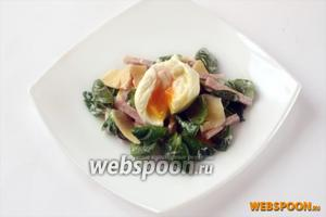 Выкладываем салат в порционные тарелки, сверху кладём яйцо. Надрезать яйцо, чтобы желток смешался с салатом, можно непосредственно во время еды.