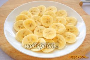 Бананы нарезать кружочками, разложить по тарелкам и сбрызнуть лимонным соком. Если неизвестно количество гостей, приготовьте салат в одной миске, так его легче будет охладить.