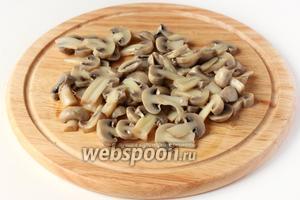 Маринованные шампиньоны нарезаем пластинками, оставив несколько целых грибочков для украшения готового салата.