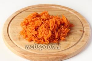 Морковь по-корейски слегка отжимаем от сока. Если морковь нарезана очень длинной соломкой, то несколько раз проходимся по ней ножом, но не измельчаем сильно!